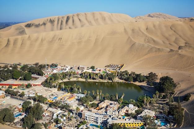 Oaza huacachina, na pustynnych wydmach w pobliżu miasta ica, peru, ameryka południowa. niezwykłe krajobrazy.
