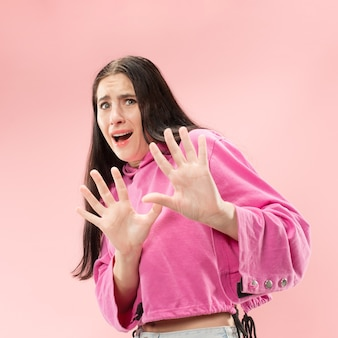 Obawiam się. strach. portret przerażonej kobiety. biznes kobieta stojąca na białym tle w modnej przestrzeni różowy
