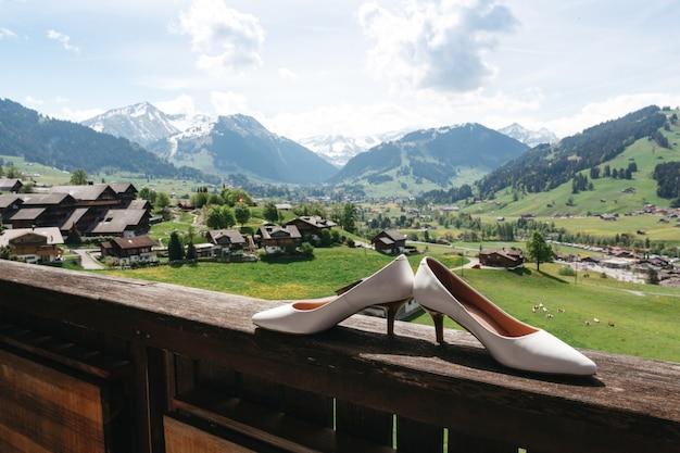 Obcasy ślubne stoją na drewnianej poręczy w szwajcarskich górach