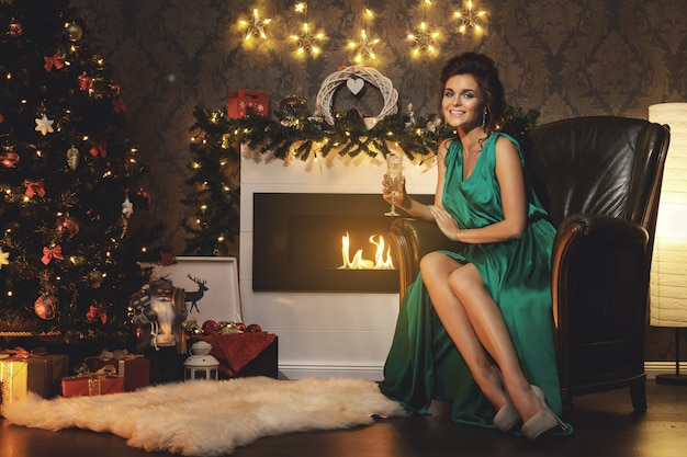 Obchody bożego narodzenia lub nowego roku. szczęśliwa kobieta przy lampce szampana.
