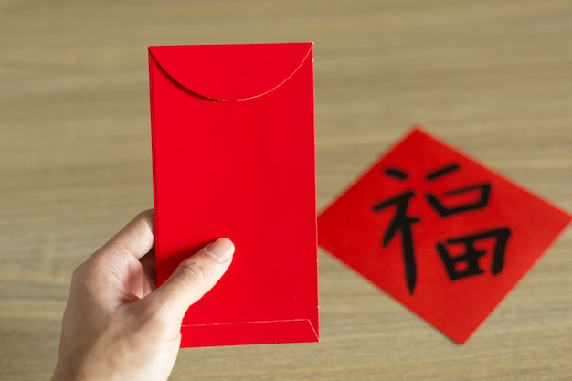 Obchody chińskiego nowego roku i księżycowego nowego roku podając czerwoną kopertę. chińskie słowo oznacza: błogosławieństwo, szczęście i szczęście