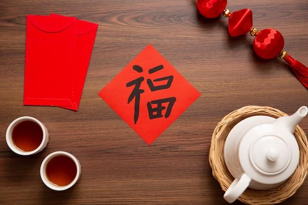 Obchody chińskiego nowego roku i nowego roku księżycowego ze złotym sztabką w postaci czerwonej koperty i gorącej herbaty. chińskie słowo oznacza: błogosławieństwo, szczęście i szczęście