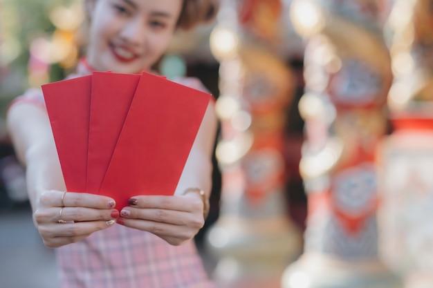 Obchody księżycowego nowego roku z czerwonymi kopertami w rękach.