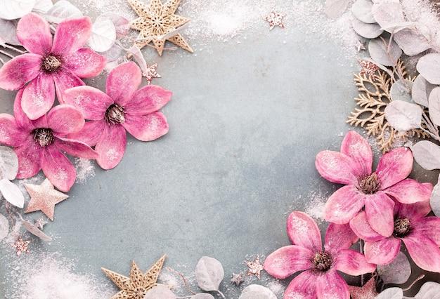 Obchody nowego roku i boże narodzenie tło z różowe kwiaty, śnieg, gwiazdy i ozdoby świąteczne widok z góry.