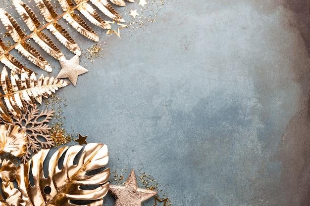 Obchody nowego roku i boże narodzenie tło z złote kwiaty, śnieg, gwiazdy i ozdoby świąteczne widok z góry.