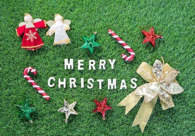 Obchody nowego roku i bożego narodzenia, widok z góry boże narodzenie alfabet i dekoracja na tle zielonej trawie
