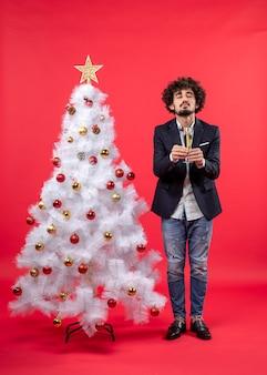 Obchody nowego roku z młodym mężczyzną trzymającym głęboko śmierdzący kieliszek wina i stojącym obok udekorowany