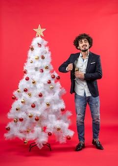 Obchody nowego roku z szczęśliwym młodym człowiekiem trzymającym kieliszek wina blisko serca