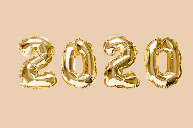 Obchody szczęśliwego nowego roku 2020. balony złotej folii cyfry 2020 na białym tle