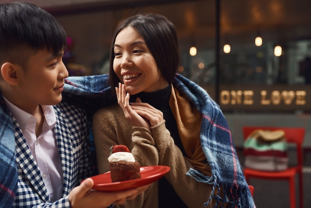 Obchody urodzin azjatyckich para w kawiarni na świeżym powietrzu.