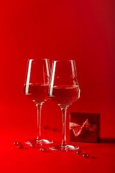 Obchody walentynek. dwa pełne kieliszki wina, ozdobne serduszka i czerwone pudełko