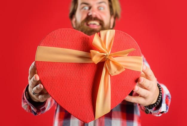 Obchody walentynek, prezent z miłością, człowiek z czerwonym prezentem kształt serca, selektywne focus.