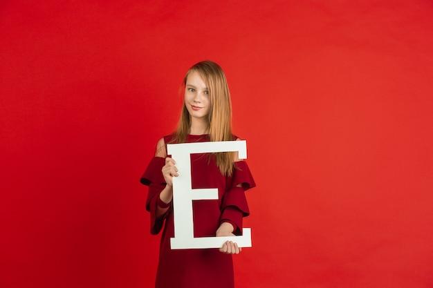 Obchody walentynek, szczęśliwa dziewczynka kaukaski trzymając list na czerwonym tle