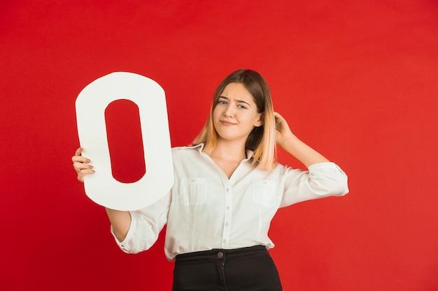 Obchody walentynek, szczęśliwa, śliczna dziewczynka kaukaski trzymając list na czerwonym studio