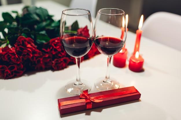 Obchody walentynek winem, świecami, czerwonymi różami i pudełkiem prezentowym w domu. romantyczna atmosfera dla zakochanych