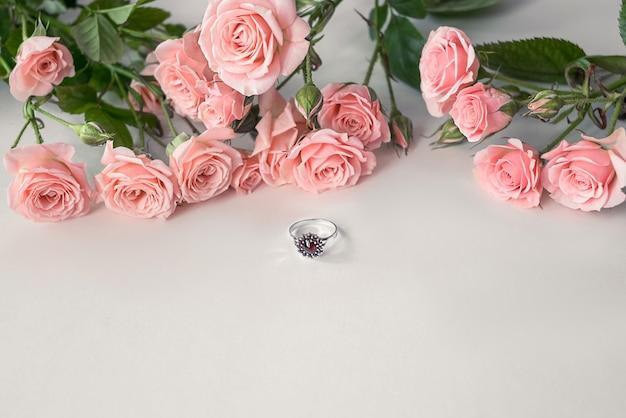 Obchody walentynek - wysadzany klejnotami pierścionek zaręczynowy leżący przed bukietem jasnoróżowych róż