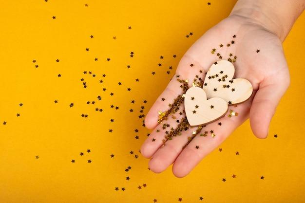 Obchody walentynki 8 marca, ręka trzyma serca na żółtym tle.