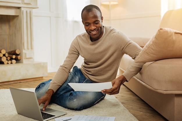 Obciążenie pracą. szczęśliwy brodaty afroamerykański mężczyzna uśmiecha się i pracuje na laptopie i trzyma kartkę papieru, siedząc na podłodze i kominku w tle