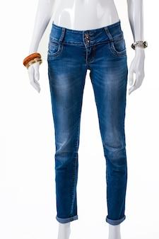 Obcisłe dżinsy i akcesoria na nadgarstki. manekin ubrany w dżinsy z bransoletkami. casualowe niebieskie spodnie na wyświetlaczu. rabaty na odzież jeansową.