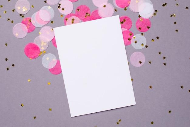 Obecna karta i różowe konfetti ze złotymi gwiazdkami na szaro