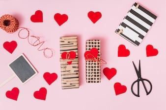 Obecne pudełka, ozdoby serca, notatnik, nożyczki i tablet