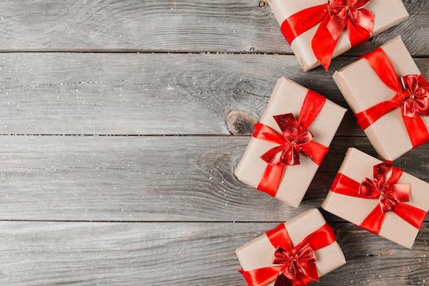 Obecne pudełka z wstążkami na drewnianym tle. świąteczna paczka na rustykalnym stole