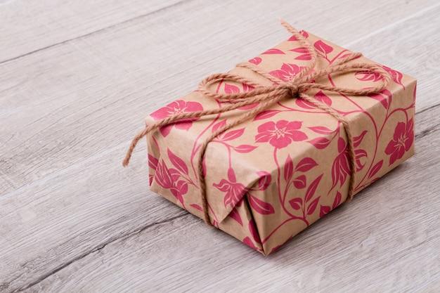 Obecne pudełko na drewnianym tle. prezent z kokardą z liny. podaruj prezenty z radością. projekt pakietu wakacyjnego.