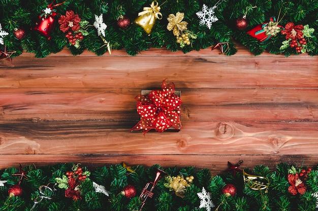 Obecne pudełko z czerwoną wstążką na tle drewna z choinką i tradycyjnymi ozdobami rekwizyty bożonarodzeniowe z miejsca kopiowania. koncepcja szczęśliwego i radosnego festiwalu.