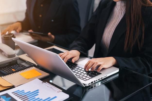 Obecne spotkanie zespołu biznesowego. profesjonalny inwestor pracujący z zadaniem menedżerów finansów. z laptopem i tabletem cyfrowym w świetle poranka