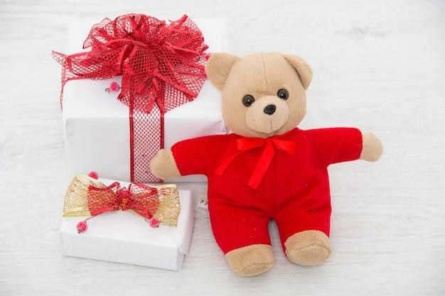 Obecny pakiet na białym tle. boże narodzenie pudełko z czerwoną wstążką i misiem walentynki. noworoczny prezent i zabawka. święto bożego narodzenia. ferie zimowe i wakacje.