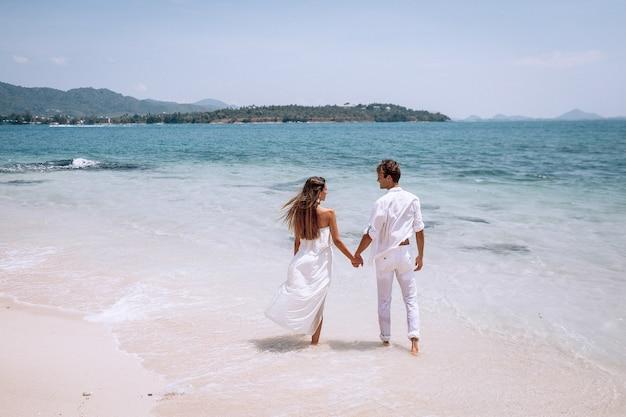 Obejmując romantyczną parę w białych ubraniach, patrząc na morze