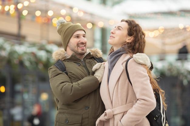 Obejmująca para patrząc na kamery z uśmiechem w winter park.