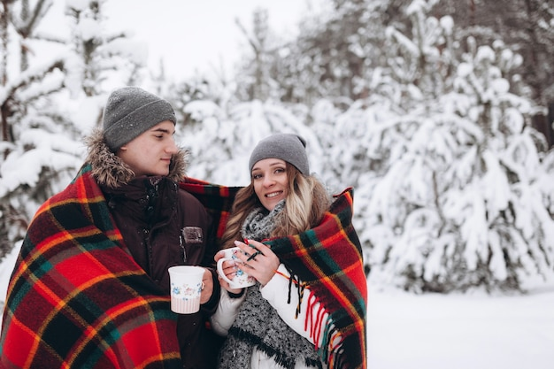 Obejmująca para patrząc na kamery z uśmiechem w winter park