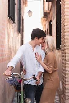 Obejmująca para pozuje z rowerowym outside