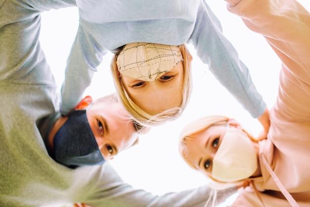Obejmujący się członkowie rodziny, uśmiechający się do kamery w maskach z tkaniny. ojciec, matka i córka chronią się przed wirusem.