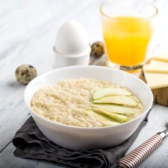 Obfite śniadanie z miski płatków śniadaniowych, jajek i soku pomarańczowego, na drewnianym stole i serwetce
