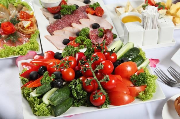Obfitość dań na stole, obok mięsnych przysmaków solona ryba i potrawa z warzywami.