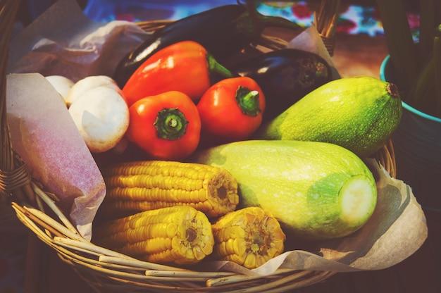Obfitość organicznych warzyw, ziół i grzybów kulinarnych w koszu. roślinna martwa natura. cukinia, pieczarki, bakłażan, pomidory i kukurydza w wiklinowym koszu