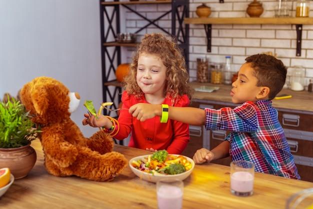 Obfity posiłek. śliczna dziewczyna utrzymuje uśmiech na twarzy, spędzając czas na kolacji w kuchni z przyjacielem