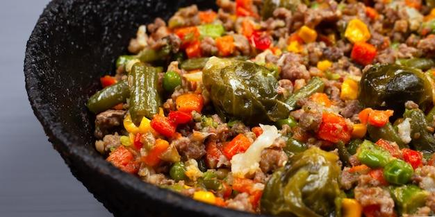 Obfity zdrowy obiad, smaczny ragout z dużą ilością sezonowych warzyw i mielonego mięsa w żeliwnej patelni z bliska, zdrowe jedzenie.