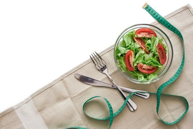 Obiad dietetyczny. na stole leżą przygotowujące do spożycia sałatki, obrus, widelec i nóż. świeże warzywa miesza się w sałatce na stole. przycięte zdjęcie