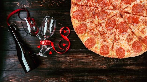 Obiad dla dwojga na cześć walentynki z pizzą i winem.