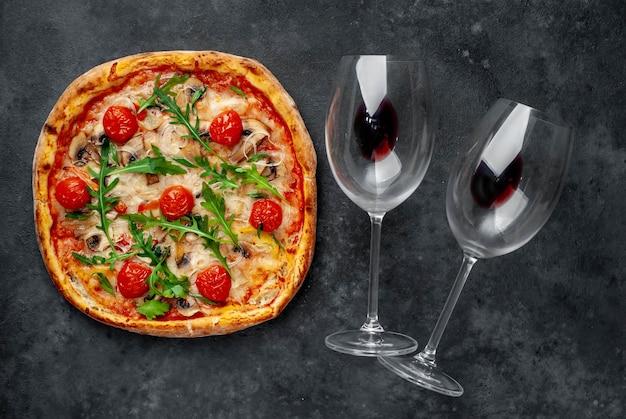 Obiad dla dwojga. pyszna włoska pizza z mozzarellą, pieczarkami, pomidorem, papryką, cebulą i butelką wina z kieliszkami.