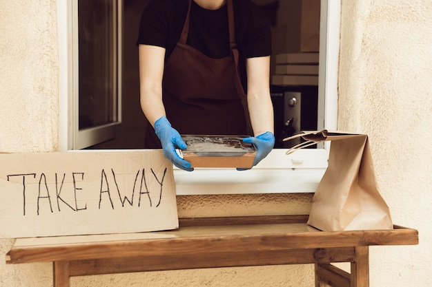 Obiad. kobieta przygotowująca napoje i posiłki, nosząca maskę ochronną i rękawiczki. bezdotykowa usługa dostawy podczas pandemii koronawirusa kwarantanny. zabierz koncepcja. kubki do recyklingu, opakowania.