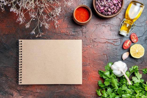 Obiad, pieprz, czosnek, cytryna, garść zieleni i notatnik na stole mieszanym