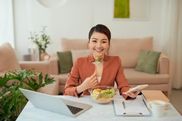 Obiad roboczy w domu atrakcyjna kobieta z laptopem je sałatkę