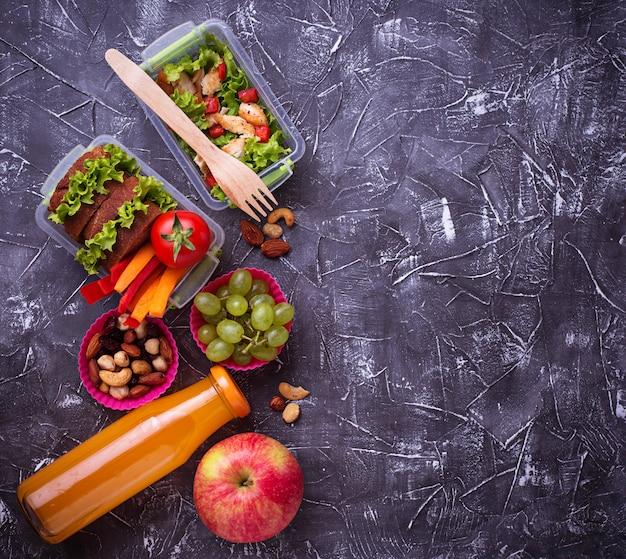 Obiad szkolny. sałatka, kanapki, owoce i orzechy
