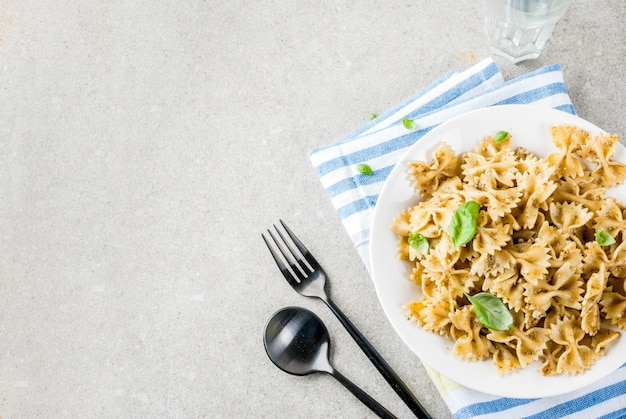 Obiad wegański. makaron farfalle z sosem pesto i liśćmi bazylii na białym talerzu, szara powierzchnia kamienia, miejsce