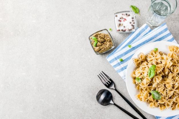 Obiad wegański. makaron farfalle z sosem pesto i liśćmi bazylii na białym talerzu szary kamień tło