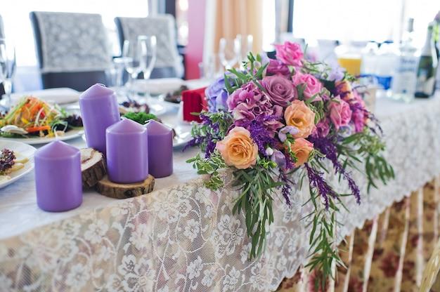 Obiad weselny w restauracji, stoły ozdobione wazonami róż.